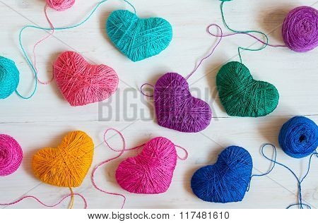 Multicolored Hearts With A Balls Of Thread On White Wooden Background