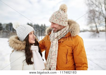 people, season, love and leisure concept - happy couple walking over winter background