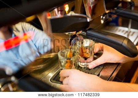 equipment, coffee shop, people and technology concept - close up of woman making coffee by espresso machine at cafe bar or restaurant kitchen