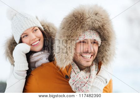 people, season, love and leisure concept - happy couple having fun over winter background