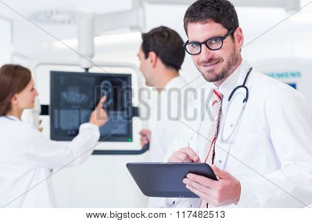 Doctor with medical team at screen of MRI machine analyzing results of scan
