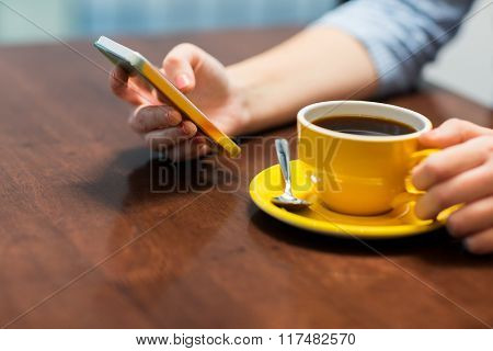 drinks, people, technology and lifestyle concept - close up of young woman with smartphone drinking coffee at cafe