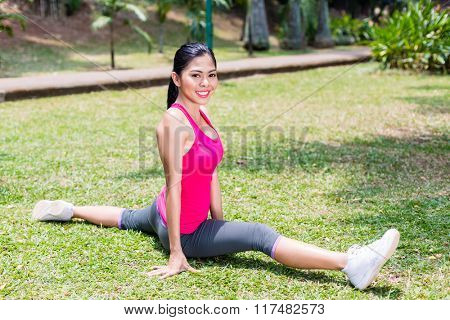 Asian woman doing splits for sport and better fitness in tropical Asian park