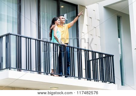 Indian woman and man standing on balcony of their new home
