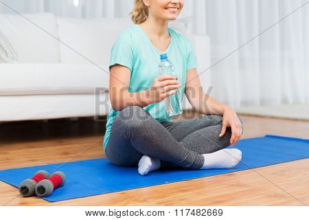 fitness, sport, people and healthy lifestyle concept - close up of happy woman with bottle of water after exercising on mat at home