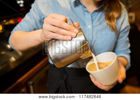 equipment, coffee shop, people and technology concept - close up of woman pouring cream to cup of coffee at cafe bar or restaurant kitchen