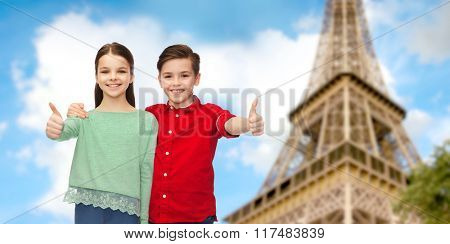 childhood, travel, tourism, gesture and people concept - happy smiling boy and girl hugging and showing thumbs up over paris eiffel tower background