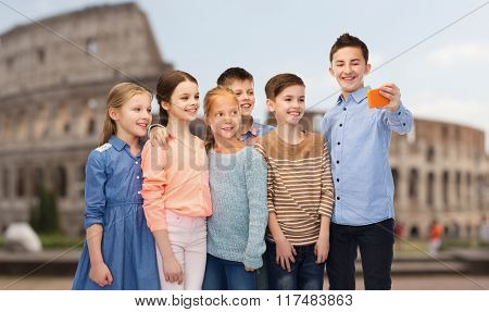 childhood, travel, tourism, technology and people concept - happy children talking selfie by smartphone over coliseum in rome