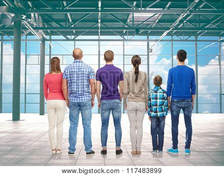 travel, vacation and people concept - group of happy people or big family from back over airport terminal window and sky background