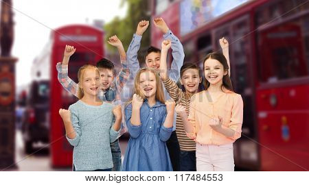 childhood, travel, tourism, gesture and people concept - happy children friends raising fists and celebrating victory over london city street background