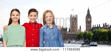 childhood, travel, tourism, friendship and people concept - happy smiling boy and girls hugging over london city background