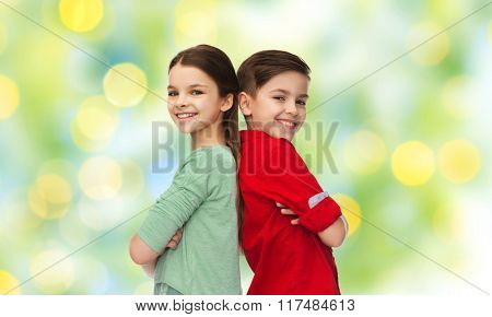 childhood, fashion and people concept - happy smiling boy and girl standing back to back over green lights background