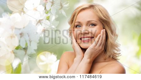 beauty, people, skincare and natural cosmetics concept - smiling woman with bare shoulders touching face over cherry blossom background