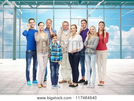 travel, vacation, communication and people concept - happy people or big family calling on smartphones over airport terminal window and sky background