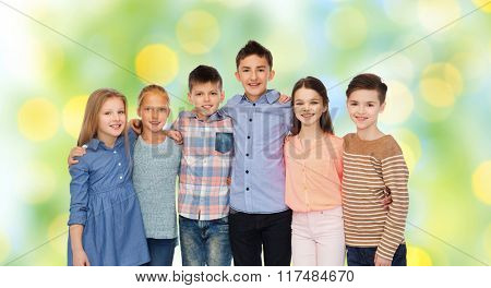 childhood, fashion, friendship and people concept - happy smiling children hugging over green lights background