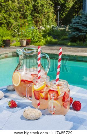 Ice cold homemade strawberry lemonade in jug and glasses with paper straws on outdoor pool side table in summer with garden in background