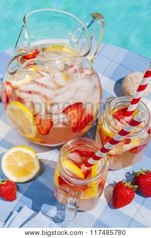 Ice cold homemade strawberry lemonade in jug and glasses with paper straws on outdoor pool side table in summer