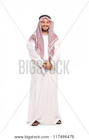 Full length portrait of a young Arab in a white robe and a red veil isolated on white background