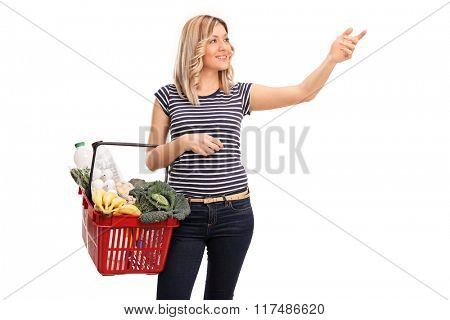 Cheerful woman holding a shopping basket with groceries and reaching for something isolated on white background