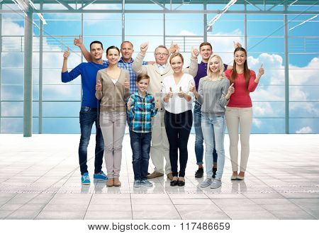 gesture, travel, vacation and people concept - group of happy people or big family showing thumbs up over airport terminal window and sky background