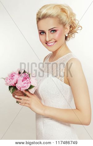 Young beautiful blonde slim happy smiling bride with stylish prom hairdo and bridal bouquet