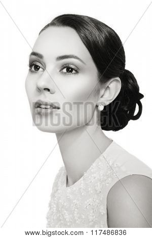 Black and white portrait of young beautiful woman with stylish hairdo over white background