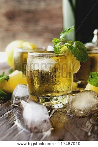 Glass of whiskey with mint and lemon