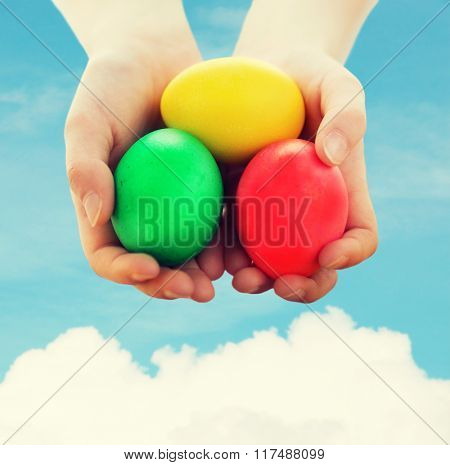 easter, holiday and child concept - close up of kid hands holding colored eggs over blue sky and white cloud background
