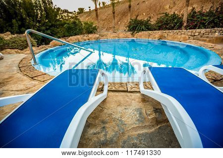 Sunloungers and swimming pool with reflected palms in water