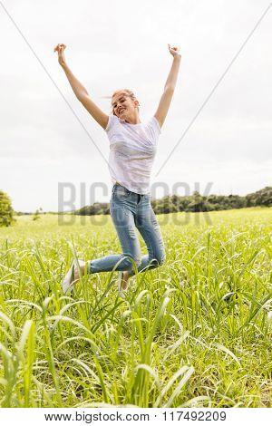happy teen girl jumping high in sugarcane field