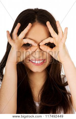 Young woman doing the perfect sign on eye.