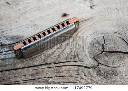 Blues Harmonica On A Wooden Background