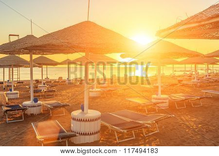 Beach with deck chairs and parasol during beautiful sunrise