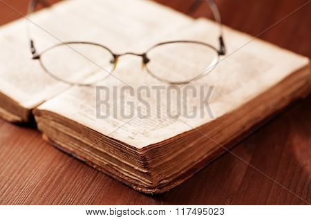Open Old Book On Wooden Table With Glasses