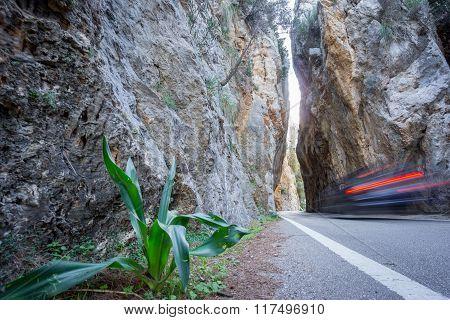 Asphalt road between rocks with car trail