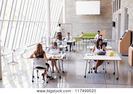 Overhead View Of Businesspeople Working At Desks In Office