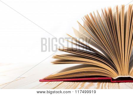 Open book at wooden table isolated on white background. Back to school. Copy space