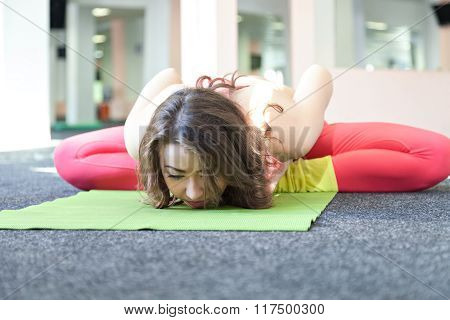 Young Female Stretching On Exercise Mat In Her Room