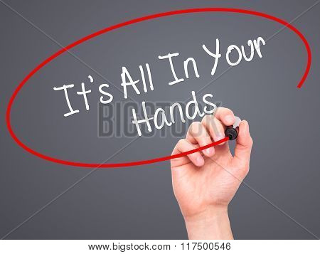 Man Hand Writing It's All In Your Hands  With Black Marker On Visual Screen.