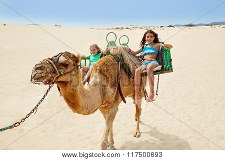 Girls riding Camel in Fuerteventura desert at Canary Islands of Spain