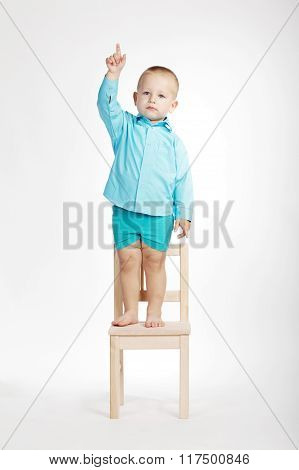 boy on chair and pointing his finger up