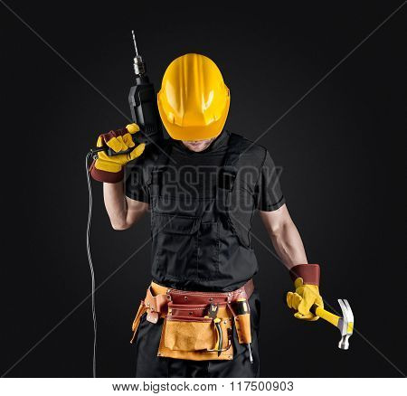 construction worker in helmet with hammer and drill