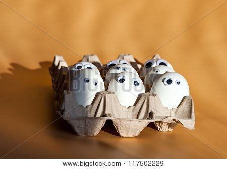 Group of eggs with false eyes in a cardboard container. Easter