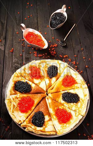 Pancakes with caviar on the wooden background