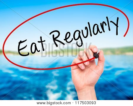 Man Hand Writing Eat Regularly With Black Marker On Visual Screen.
