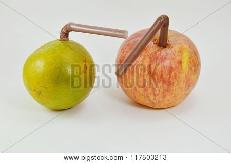 straw stab in red apple and orange