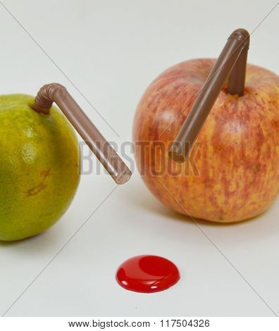 orange and apple stab by straw with liquid red dot drop