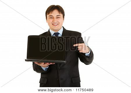 Smiling modern businessman pointing finger on laptops blank screen isolated on white
