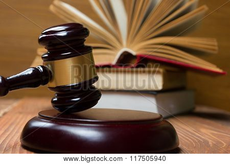 Law book with wooden judges gavel on table in a courtroom or law enforcement office.