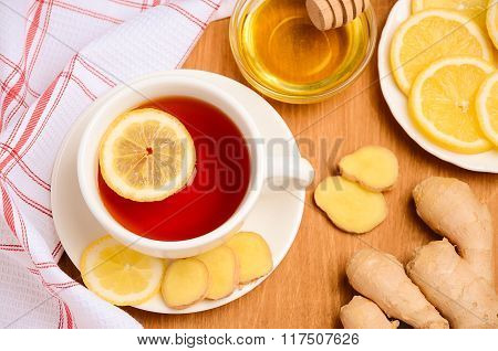Black tea with lemon, ginger and honey on the wooden table.